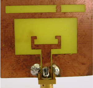 Rectangular slot antenna with C-shaped stub and metal pads